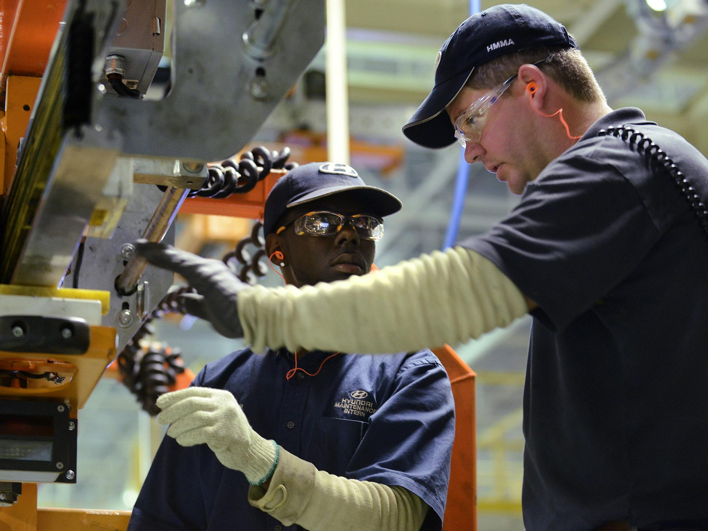 Trenholm State Technical College student Darien Fails, left, is instructed by Ben Rieves in the stamping shop at Hyundai Motor Manufacturing in Montgomery, Ala. in August of 2014 as part of a student hands-on program at the plant.