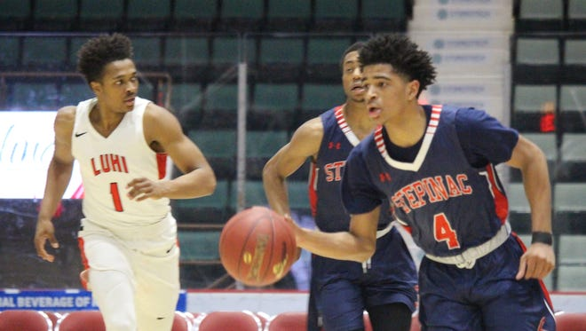 Stepinac's R.J. Davis (4) dribbles up court during his team's Class AA semifinal of the Federation Tournament of Champions against Long Island Lutheran at Cool Insuring Arena in Glens Falls on March 23, 2018.