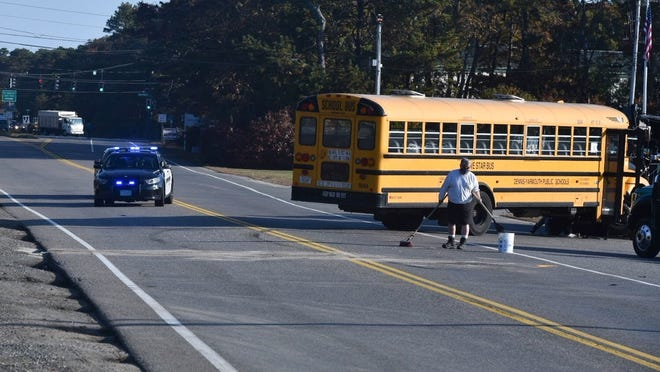 A Dennis-Yarmouth Regional School District bus sits along Willow Street in West Yarmouth following a crash Friday with an Eversource truck. No injuries were reported, according to police.