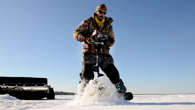 Kurt Hanson, of Finquest guide services, Dyckesville, gets set up for ice fishing along the east shore of the bay of Green Bay.