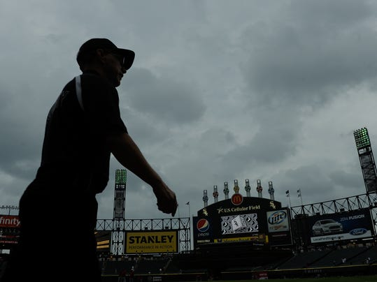Clouds hover over the field as a security guard walks towards the outfield before a baseball game between the Los Angeles Angels and the Chicago White Sox on Monday, June 30, 2014, in Chicago. (AP Photo/Matt Marton)