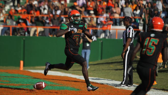 Florida A&M University wide receiver Brandon Norwood drops the ball as he runs toward a teammate to celebrate his touchdown.