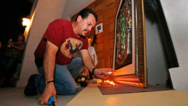 Gabrial Noguez places candles around a painting of the Virgin Mary in honor of Father Kenneth Walker Thursday evening, June 12, 2014 at the site of the shooting at Mater Misericordiae (Mother of Mercy) Mission in Phoenix, AZ. Father Kenneth Walker, 28, was shot and killed and Father Joseph Terra was wounded at the Catholic church Wednesday night near the state Capitol.