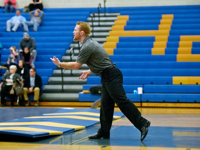 Chance Marsteller directs a wrestler on the mat during