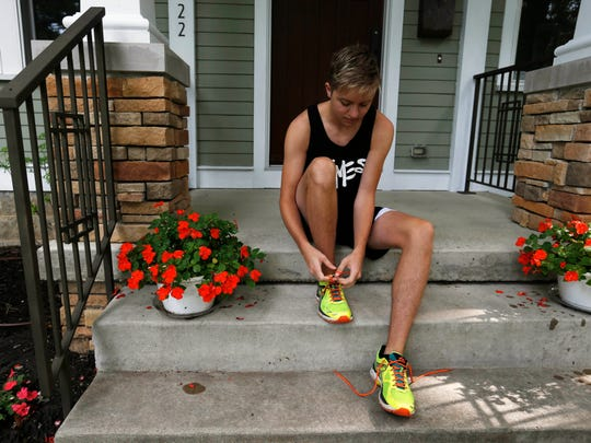 Ben Christiason laces up his shoes Tuesday, July 12, 2016, as he gets ready to go for a run in Cedar Falls. Christiason ran track as a freshman on the girls' team at Cedar Falls High School before his transition from female to male. He finished his senior year as a member of the boys' track team.