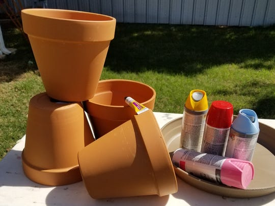 Materials needed for flower pot bird bath include pots and spray paint.