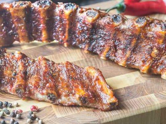 Baby back ribs on a cutting board.