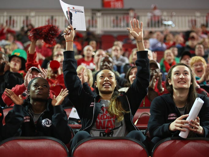 Louisville Cardinals Monny Niamke, from left, Antonita Slaughter, and Megan Deines cheer with fans during NCAA seed announcements Monday evening in the KFC Yum Center. March 17, 2014