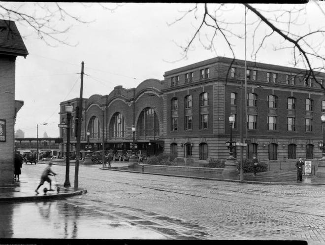 This photograph, circa 1913-20, shows the Claude Bragdon-designed New York Central Railroad Station on a rainy day, a line of automobiles waiting at the entrance.