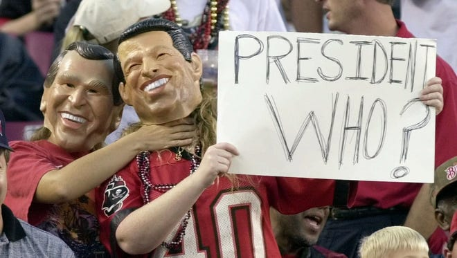 In this Nov. 12, 2000, file photo, fans are dressed as George W. Bush and Al Gore during a Tampa Bay Buccaneers game.