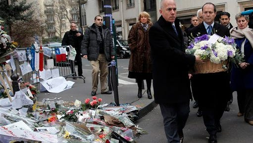 Jerusalem Mayor Nir Barkat, right,  lays a wreath of flowers next to Charlie Hebdo newspaper office in Paris, Wednesday, Jan. 21, 2015, to commemorate those killed in the Paris shootings earlier this month. The shootings have led France to rethink its response to the terrorist threat in Europe and seek new measures to protect itself.