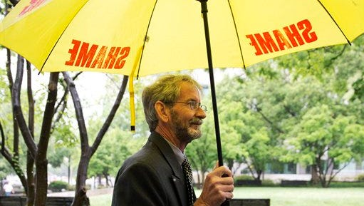 """Carrying an umbrella that says """"shame"""" on it, Douglas Hughes of Florida arrives at federal court in Washington, Thursday, May 21, 2015. Hughes, who flew a gyrocopter through some of America's most restricted airspace before landing at the Capitol pleaded not guilty on Thursday to the six charges he faces.  (AP Photo/Jacquelyn Martin)"""