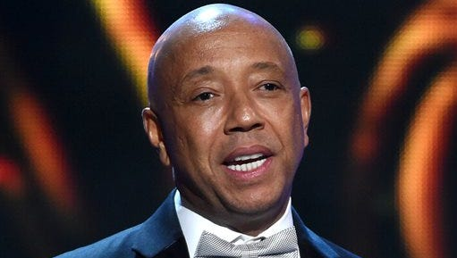 FILE - In this Feb. 6, 2015, file photo, hip-hop mogul Russell Simmons presents the Vanguard Award on stage at the 46th NAACP Image Awards in Pasadena, Calif. RushCard, the pre-paid debit card backed by Simmons, is creating a multi-million dollar fund to help cover the costs that its customers had while the card was beset by technical problems. RushCard customers who had late fees tied to bills or any other financial setbacks as a direct result of their money being locked up with RushCard will be compensated, the company said. (Photo by Chris Pizzello/Invision/AP, File)