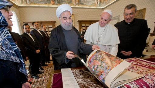 Iranian President Hassan Rouhani, left, leafs through a book he gave to Pope Francis as a gift, during their private audience at the Vatican,Tuesday, Jan. 26, 2016. Iran's president has paid a call on Pope Francis at the Vatican during a European visit aimed at positioning Tehran as a potential top player in efforts to resolve Middle East conflicts, including Syria's civil war. (AP Photo/Andrew Medichini, Pool)