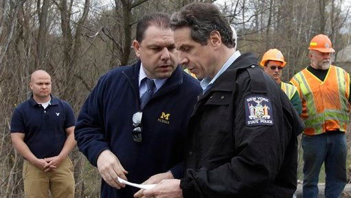 Gov. Andrew Cuomo, right, and aide Joseph Percoco tour an area hit by a spring storm in Moriah, N.Y., on April 29, 2011.