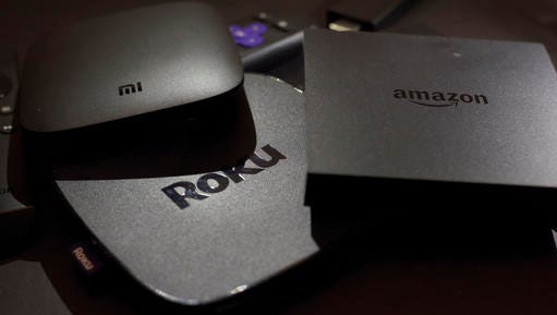 This Wednesday, Nov. 16, 2016 photo shows Xiaomi's Mi Box, left, the Roku Premiere, center, and the Amazon Fire TV streaming TV devices in New York.  Your streaming TV options just got better and cheaper. Features that once required a $100 device can now be had for as little as $30. A cheap device is fine for getting TV shows and movies from most popular services onto a big-screen TV, as long as it's a regular, high-definition set.