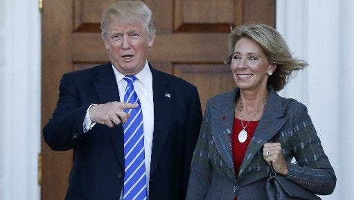 In this Nov. 19, 2016 file photo, President-elect Donald Trump and Betsy DeVos pose for photographs at Trump National Golf Club Bedminster clubhouse in Bedminster, N.J. Trump has chosen charter school advocate DeVos as Education Secretary in his administration.