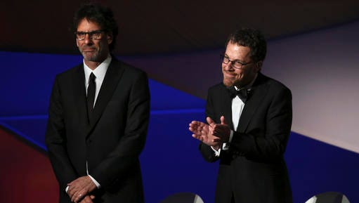 "File-This May 13, 2015, file photo shows Jury presidents Ethan Coen, right, and Joel Coen standing on stage during the opening ceremony at the 68th international film festival, Cannes, southern France.  The Coen will polish the script for a planned ""Scarface"" remake. Universal Pictures announced Friday, Feb. 10, 2017, that ""an explosive reimagining"" of the gangster classic will be released in August 2018. Diego Luna is set to star in the role famously played by Al Pacino in Brian De Palma's 1983 remake of the 1932 original."
