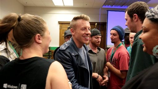 Rapper Macklemore greets people as the King County Drug Court celebrates its 20th anniversary on Tuesday in Seattle. The award-winning rapper spoke about his experiences as a teenager with a drug and alcohol addiction that landed him in juvenile drug court.