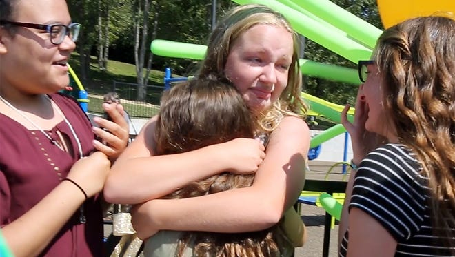 Rachel Ritchie, center, hugged well wishers who turned out to see the opening of Rachel's Fun for Everyone Playground in Vine Grove.