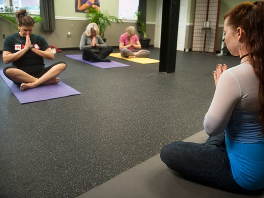 Yoga instructor Sarah LaFleur, a 2009 Rancocas Valley High School graduate, right, leads a yoga class with Rancocas Valley High School staffers, from left, guidance counselor Lia Aloi, curriculum secretary Sandy Hager, and child development teacher Diane Holzschuh, as part of the school's staff wellness program, which helps promote healthy lifestyle choices.