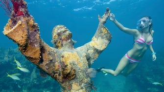 Snorkeler Katherine Wieland examines the Christ of the Abyss statue in the Florida Keys National Marine Sanctuary off Key Largo, Fla. This nine-foot-tall, 4,000 pound replica of a similar statue, located in the waters off the coast of Italy, is submerged in 25 feet of water at Key Largo Dry Rocks.