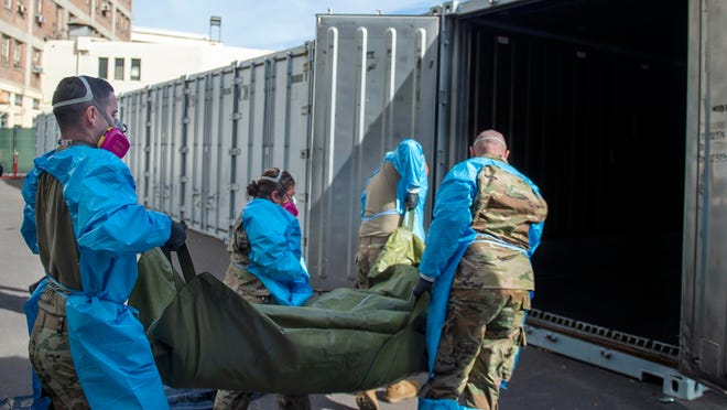 National Guard members assist with processing COVID-19 deaths, placing victims' bodies into temporary storage at the medical examiner-coroner's office in Los Angeles on Jan. 12.