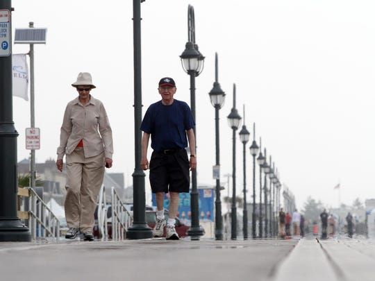 Bob and Barbara Hughes, owners of a Belmar condo, walk the boardwalk, Monday, June 15, 2015, a day after crowds attending the annual Belmar Seafood forced access to the town to be shut down for several hours.