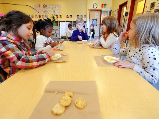 Children eat rice cakes and pineapple as a snack in their preschool class at IU Health Day Nursery, Wednesday, Feb. 26, 2014, in Indianapolis.