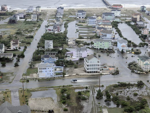 This Friday, July 4, 2014 aerial photo provided by the U.S. Coast Guard shows flooding caused by Hurricane Arthur on the Outer Banks of North Carolina.