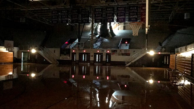 The west side of the Muncie Fieldhouse as seen from the inside. Daylight pours in a massive hole in the ceiling as a ruptured sprinkler line, believed to be at least a 4 inch pipe, pours water onto the upper level bleachers and, ultimately, onto the floor.