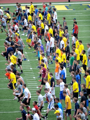Quarterbacks stretch out at Michigan Stadium during