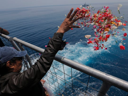 A relative sprinkles flowers for the victims of the crashed Lion Air Flight 610 from an Indonesia navy ship Nov. 6, 2018, in the waters where the airplane is believed to have crashed near Tanjung Karawang, Indonesia.