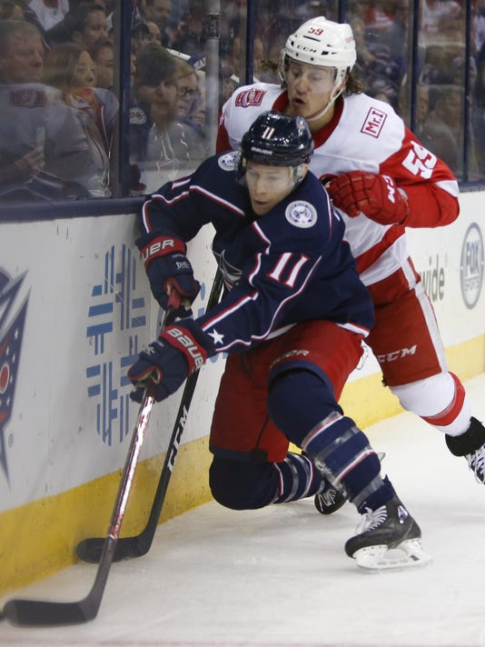 Columbus Blue Jackets' Matt Calvert, left, takes the puck away from Detroit Red Wings' Tyler Bertuzzi during the second period of an NHL hockey game Friday, March 9, 2018, in Columbus, Ohio. (AP Photo/Jay LaPrete)