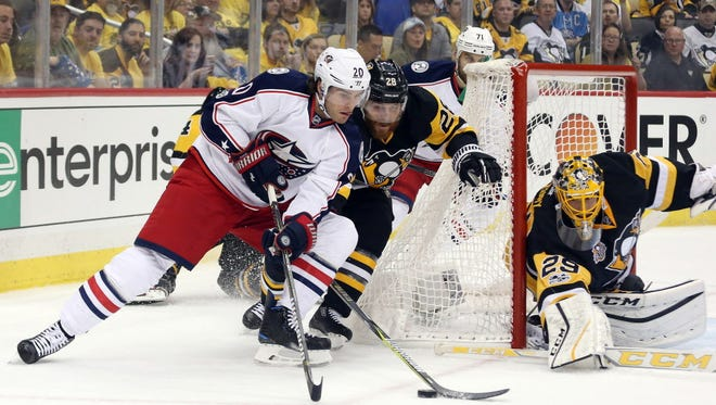Columbus Blue Jackets left wing Brandon Saad (20) skates with the puck as Pittsburgh Penguins defenseman Ian Cole (28) and goalie Marc-Andre Fleury (29) defend during the first period.