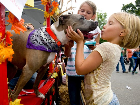 "Adelyn Gamblin, 7, of Evansville (right) receives a smooch from Dottie in the Posey County Pound Puppies ""kissing booth"" at Kunstfest 2015 in New Harmony."