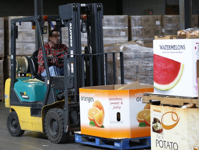 Montez Lee, a warehouse worker at the Freestore Foodbank warehouse, moves boxes of food around in preparation for loading on the trucks.
