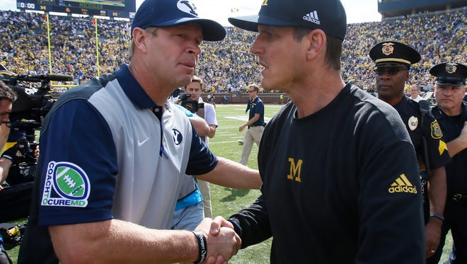 Brigham Young coach Bronco Mendenhall shakes hands with Michigan coach Jim Harbaugh after Michigan's 31-0 win Saturday.