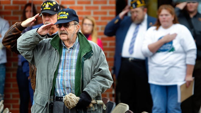 November 11, 2014 - Brothers Doug Carr, 71, (left) and Billy Carr, 86, both of whom served in the U.S. Army, salute as the colors are retired after a Veterans Day memorial service at the West Tennessee Veterans Cemetery Tuesday afternoon.