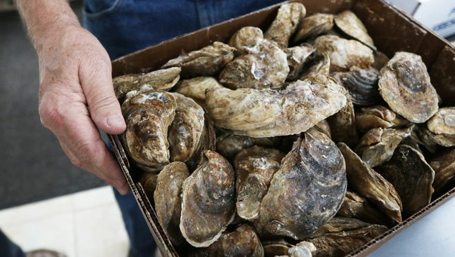 Maurice Smith Jr. owner of Maurice's Seafood Market shows a box of frozen James River oysters in the shell at his shop in Staunton on Thursday, Nov. 30, 2017.
