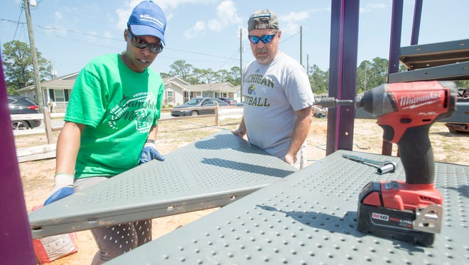 Homeowner Nateisha Gulley, left, volunteer Joe Ocobock move a piece of playground into place at Habitat for Humanity's Camshire Meadows community in Pensacola on Friday, April 13, 2018.