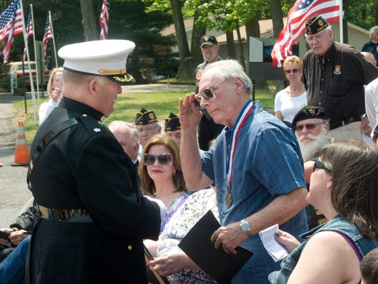 Anthony Caravello (right) salutes Col. Al Bancroft after receiving a special award on behalf of his cousin James Castaldi, who was killed in Vietnam.