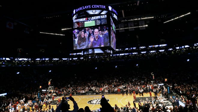 Britain's Prince William, right, and Kate, Duchess of Cambridge, acknowledge the crowd during the second half of an NBA basketball game between the Brooklyn Nets and the Cleveland Cavaliers, Monday, Dec. 8, 2014, in New York. (AP Photo/Frank Franklin II)