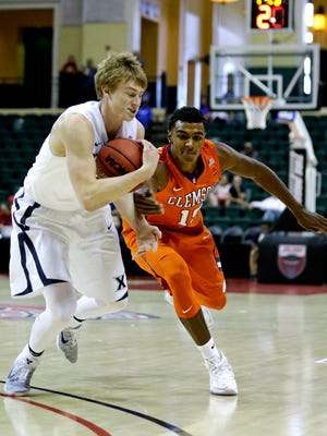 Xavier's J.P. Macura, left, is fouled by Clemson's Donte Grantham while going for a loose ball during the first half of an NCAA college basketball game at the Tire Pros Invitational tournament, Friday, Nov. 18, 2016, in Lake Buena Vista, Fla.