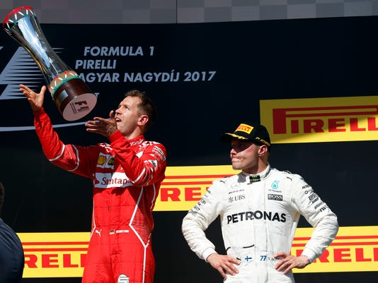 Third placed Mercedes driver Valtteri Bottas of Finland, right, watches as Ferrari driver Sebastian Vettel of Germany celebrates with hisntrophy after winning the Hungarian Formula One Grand Prix, at the Hungaroring racetrack in Mogyorod, northeast of Budapest, Sunday, July 30, 2017. (AP Photo/Darko Bandic)