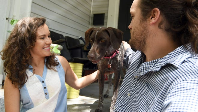 Nadine Armstrong and husband Tyler Holston sit with their dog June on their front porch in Hattiesburg on Thursday, May 3, 2018. June was recently poisoned over the weekend by someone throwing a poison-laced hot dog into their back yard.