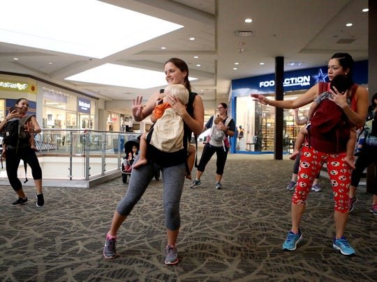 Mothers hold their children as they work out during The Mommy & Me Fitness Club on Tuesday, Jan. 3, 2017, at La Palmera Mall in Corpus Christi.