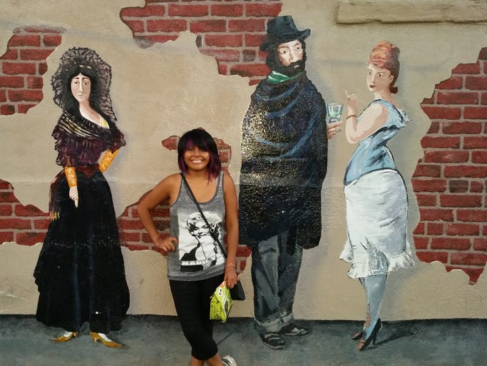 Woman posing next to painted human figures