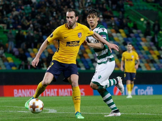 Atletico's Diego Godin, left, challenges for the ball with Sporting's Marcos Acuna during the Europa League quarterfinal second leg soccer match between Sporting CP and Atletico Madrid at the Alvalade stadium in Lisbon, Thursday, April 12, 2018. (AP Photo/Armando Franca)