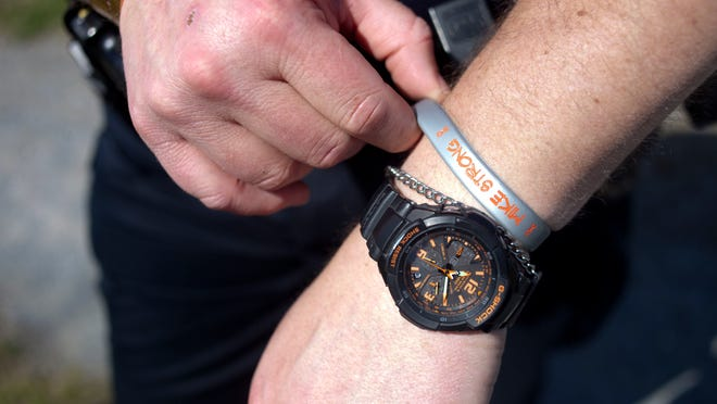 Officer Josh Flore, 43, shows his bracelet in support of Officer Mike Thomas' fight against Leukemia at the Shelburne Police Department on May 6. The bracelets are being sold for $5 each to raise money in hopes to cover various expenses during Thomas' treatment.